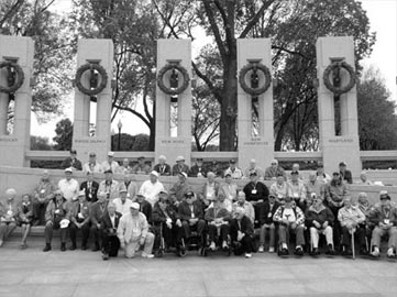 AT THE WWII MEMORIAL - Veterans from Herkimer County pose in front of the World War II Memorial in Washington, D.C., on Friday. Bystanders cheered the group and used the veterans' cameras to take photographs for them.